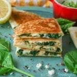 Stack of cheesy spinach quesadillas on a blue board next to baby spinach, feta, chili flakes and cut lemon.