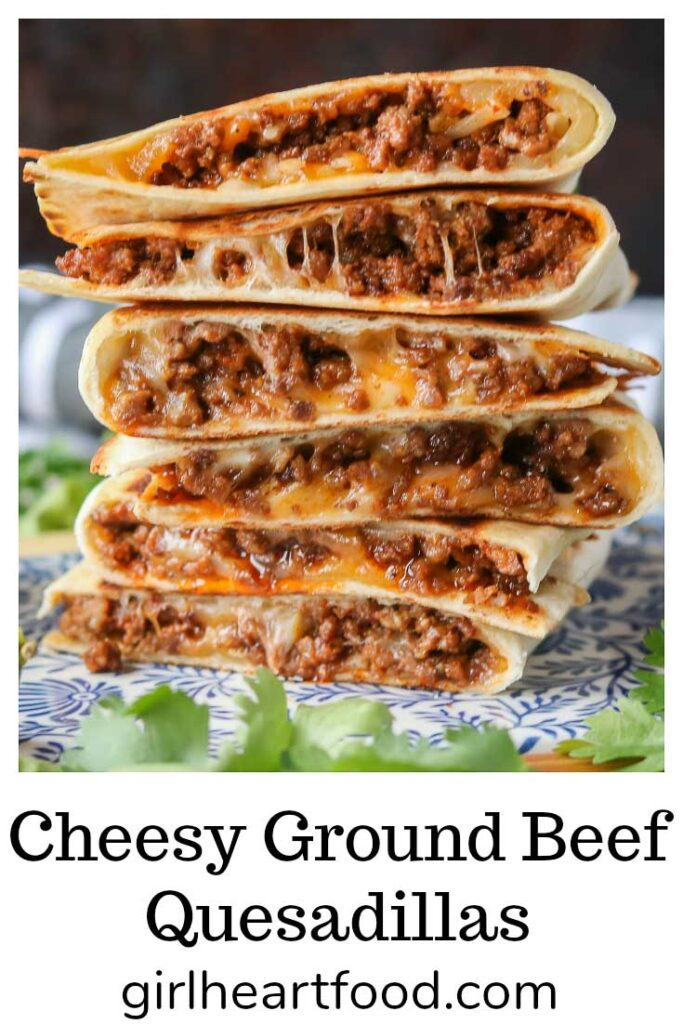 Stack of six cheesy ground beef quesadillas on a blue and white platter.