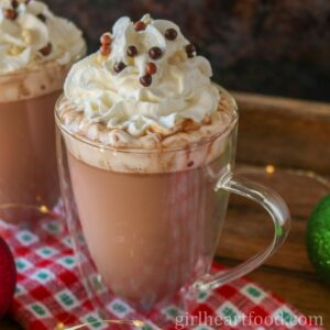 Glass mug of orange hot chocolate with whipped cream and candy on top.