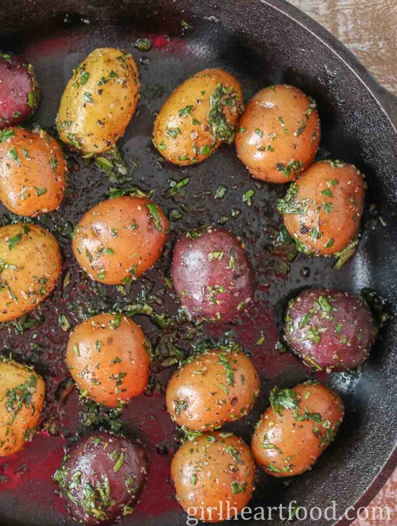 Baby potatoes with herbs in a cast-iron skillet before being roasted.