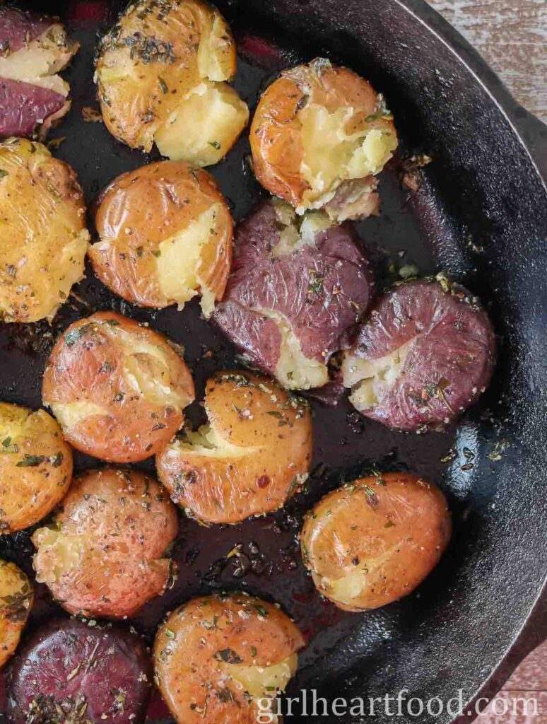 Smashed baby potatoes with herbs in a cast-iron skillet.