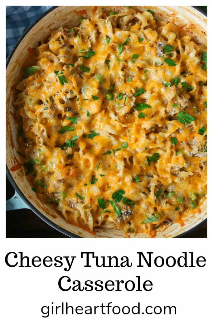 Dish of cheesy tuna noodle casserole garnished with parsley.