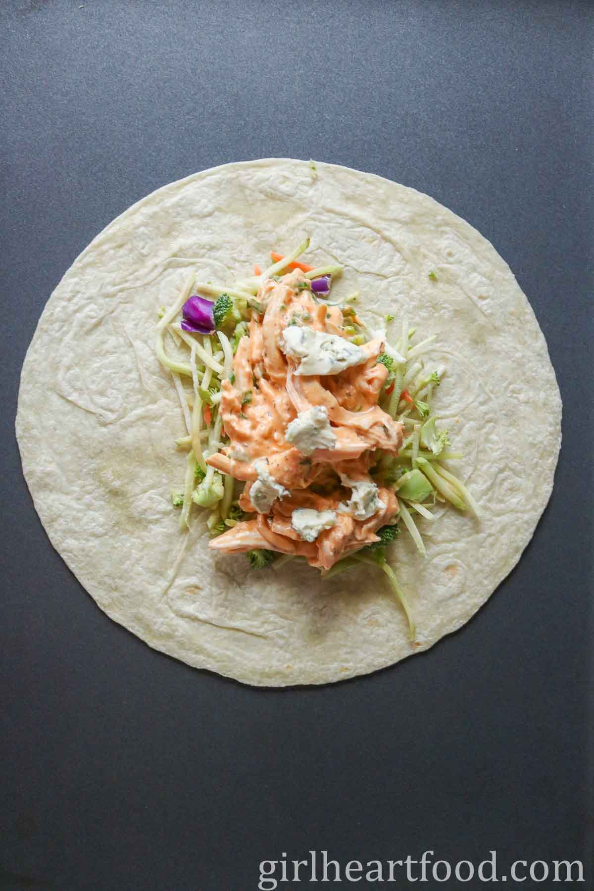Buffalo chicken wrap with salad mix and blue cheese before being rolled up.