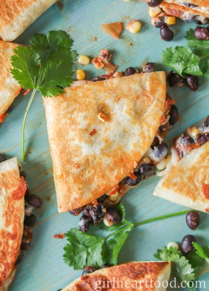 Black bean quesadillas on a blue board next to fresh cilantro.
