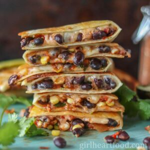 Tall stack of cheesy black bean and corn quesadillas.