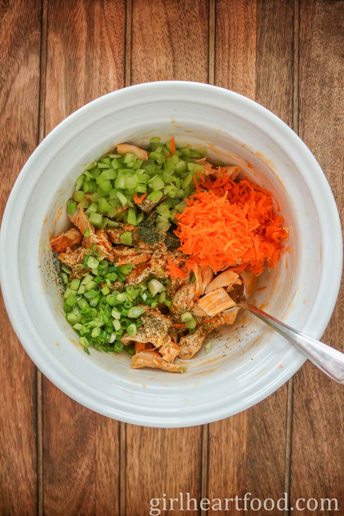 Buffalo chicken mixture with veggies in a white bowl and a spoon dunked into the mixture.