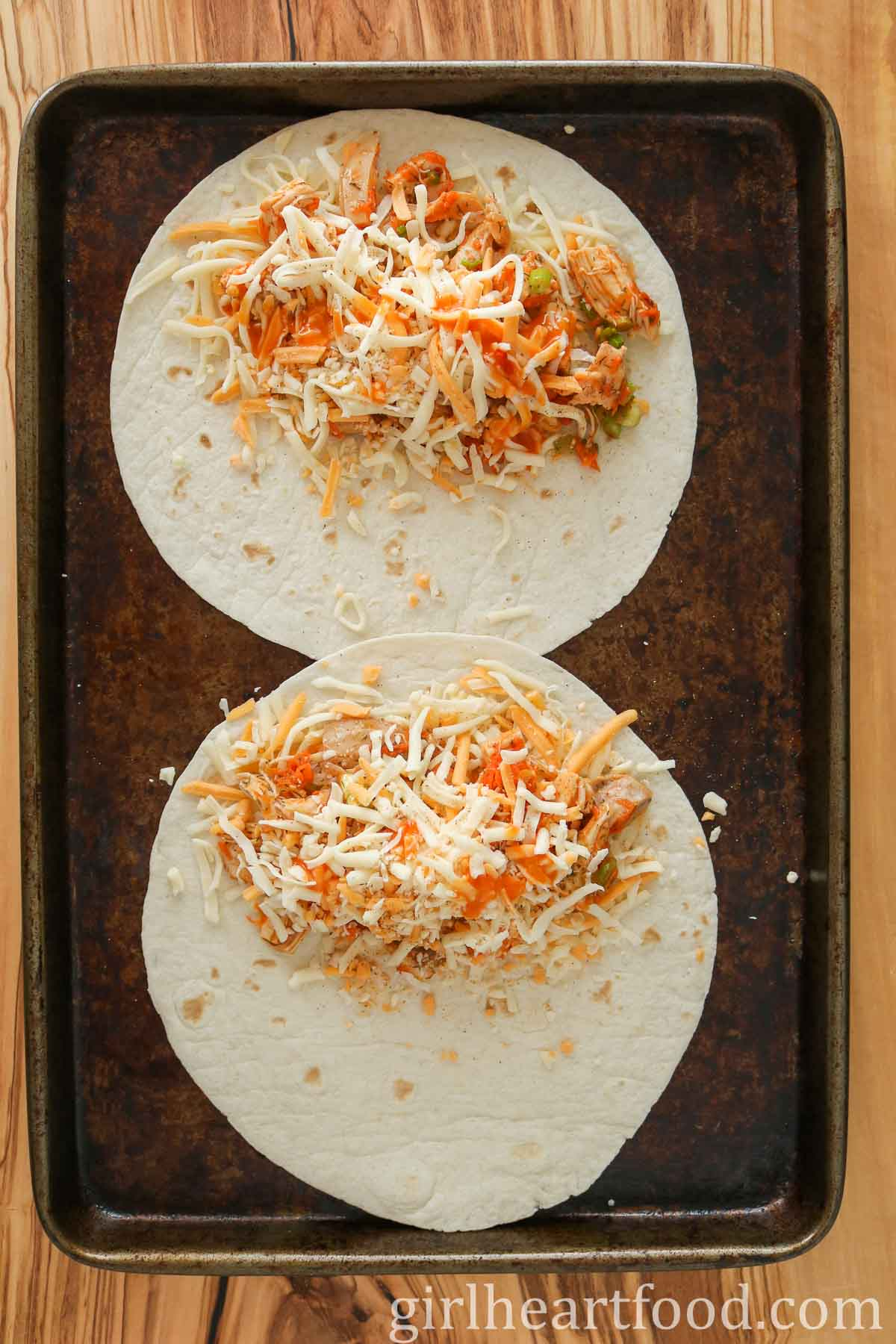Two tortillas topped with buffalo chicken and cheese on a sheet pan.