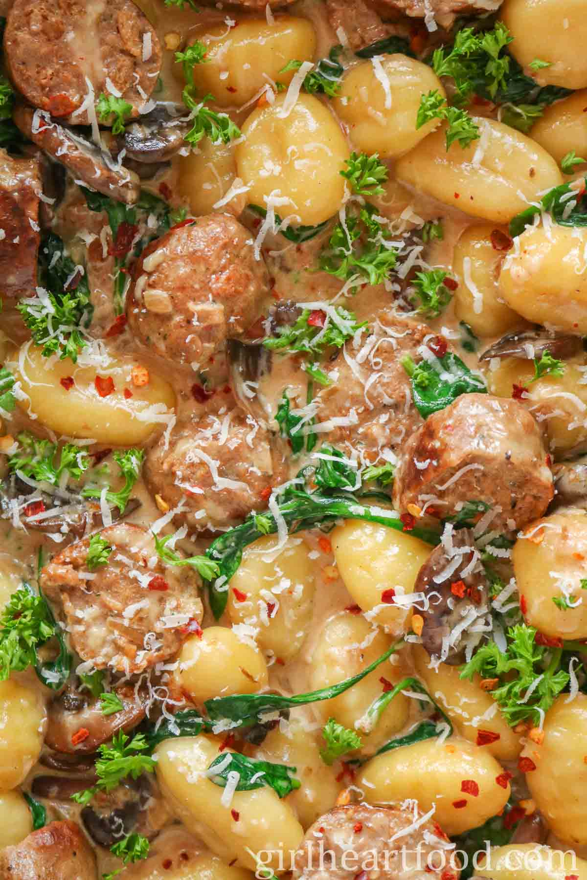Close-up of gnocchi, sausage, mushrooms and spinach in cream sauce.