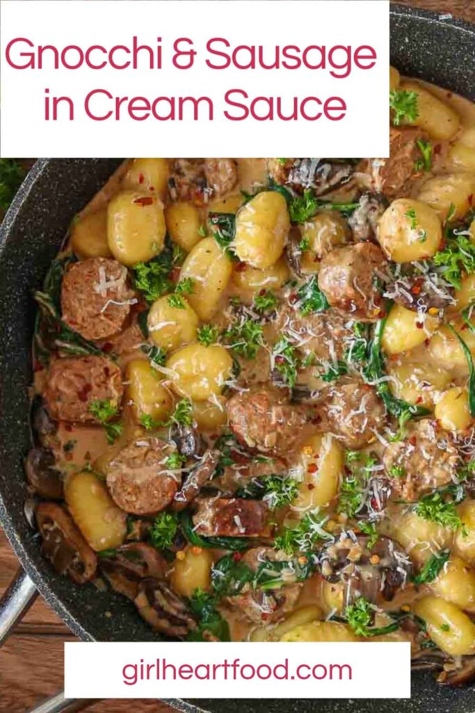 Close-up of a pan of sausage, gnocchi, mushrooms and spinach in cream sauce.