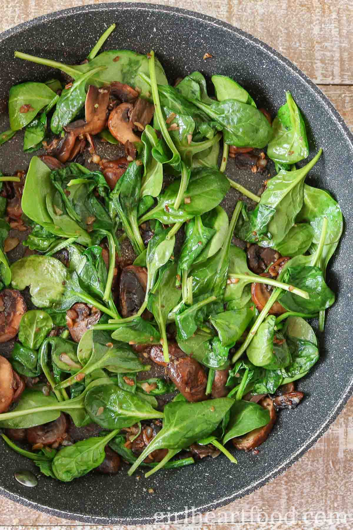 Cooked mushrooms and baby spinach in a non-stick-pan.