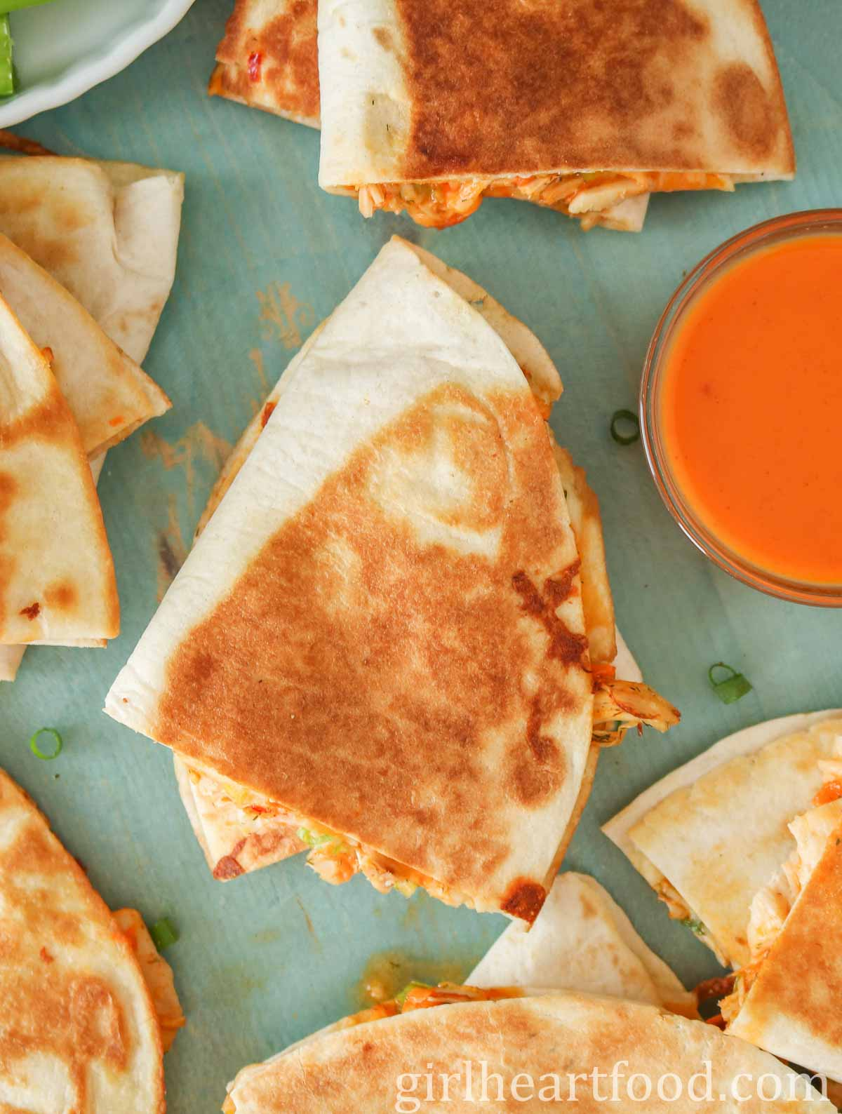 Crispy quesadillas on a blue board next to a small dish of buffalo hot sauce.
