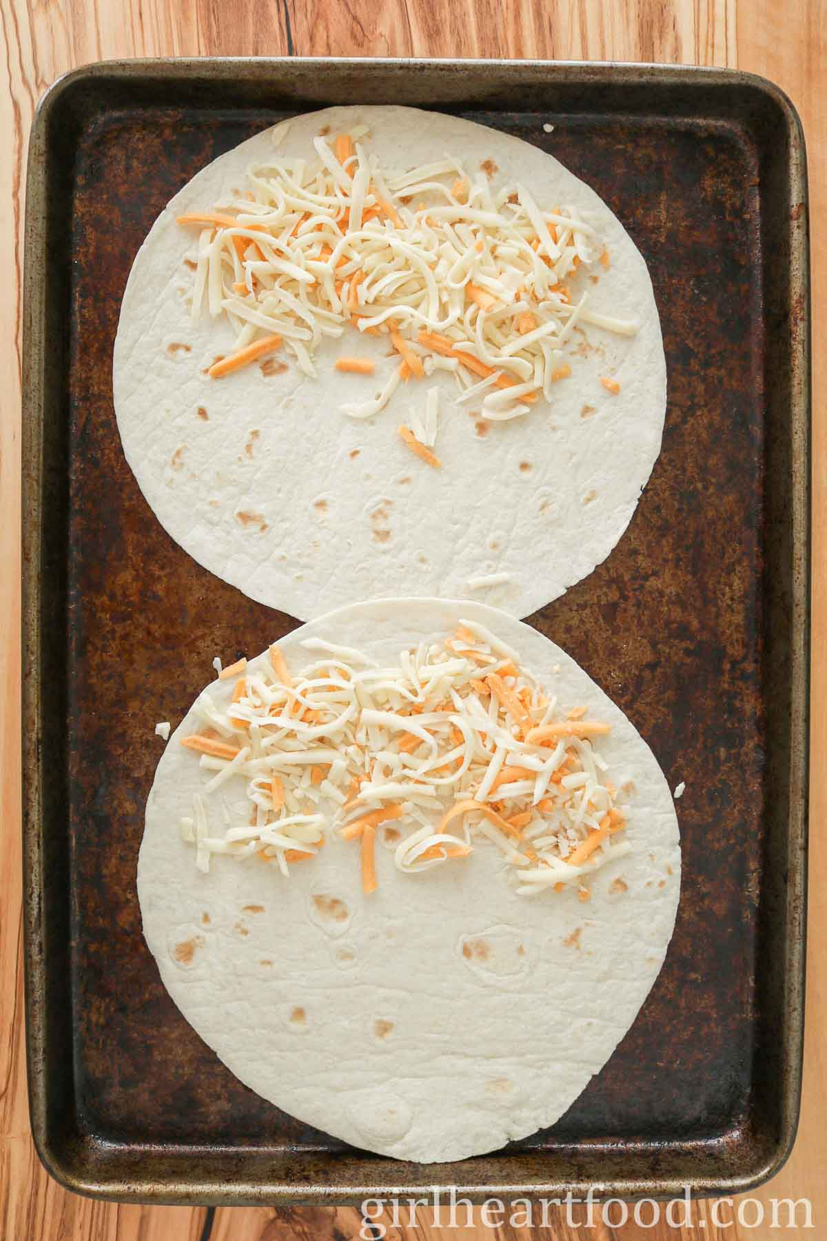 Two flour tortillas topped with shredded cheese on a sheet pan.