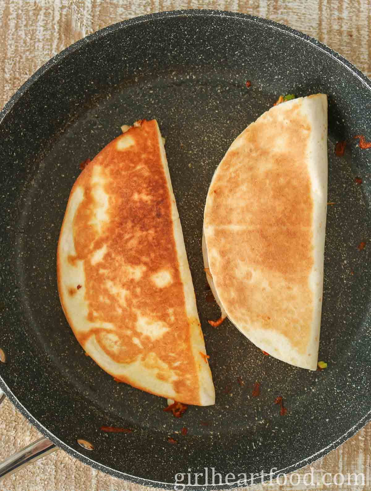 Two crispy quesadillas in a non-stick pan.