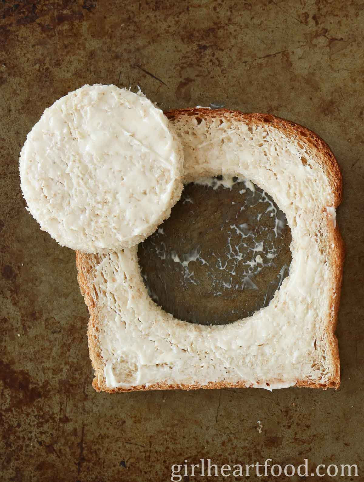 Slice of buttered bread with a circle cut out, leaving a hole in the centre of the bread.