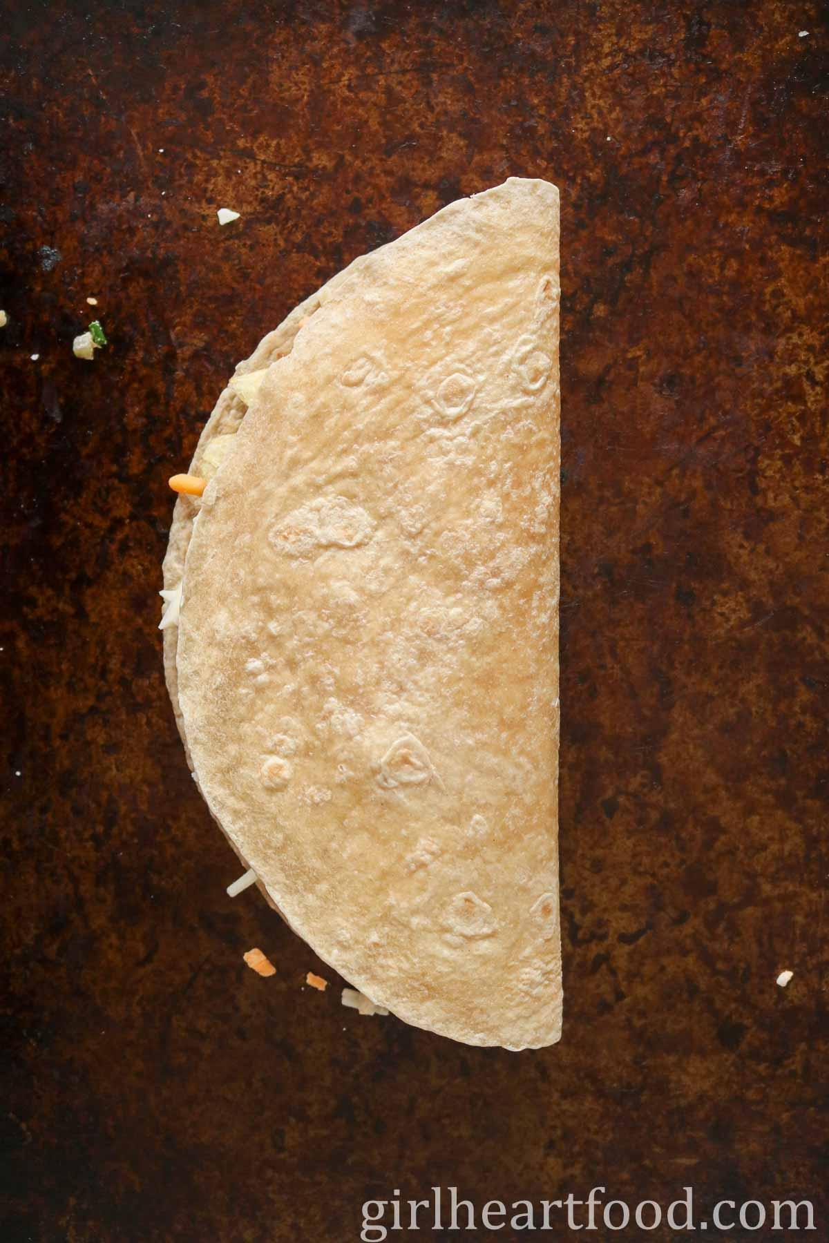 Tuna quesadilla on a sheet pan before being pan fried.