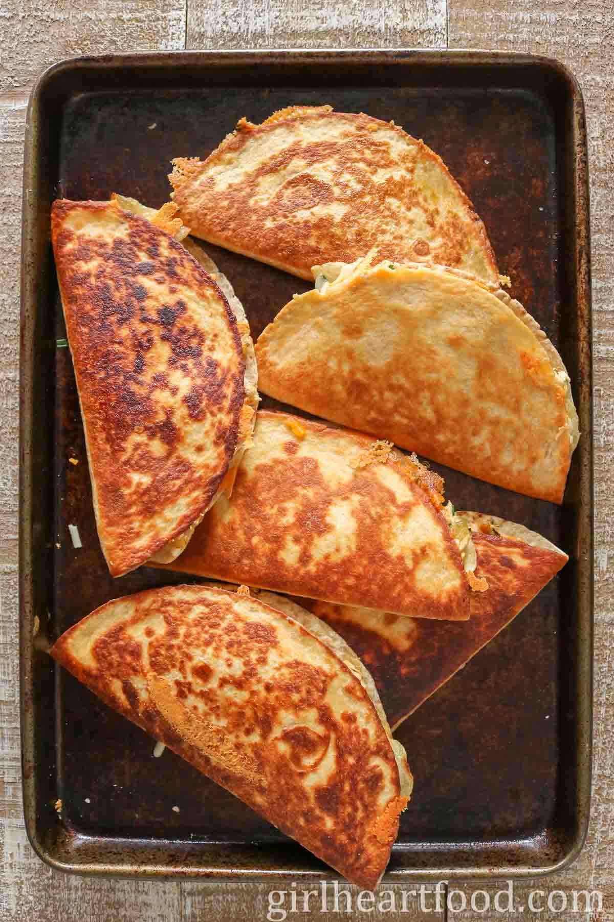 Crispy tuna and cheese quesadillas on a sheet pan.