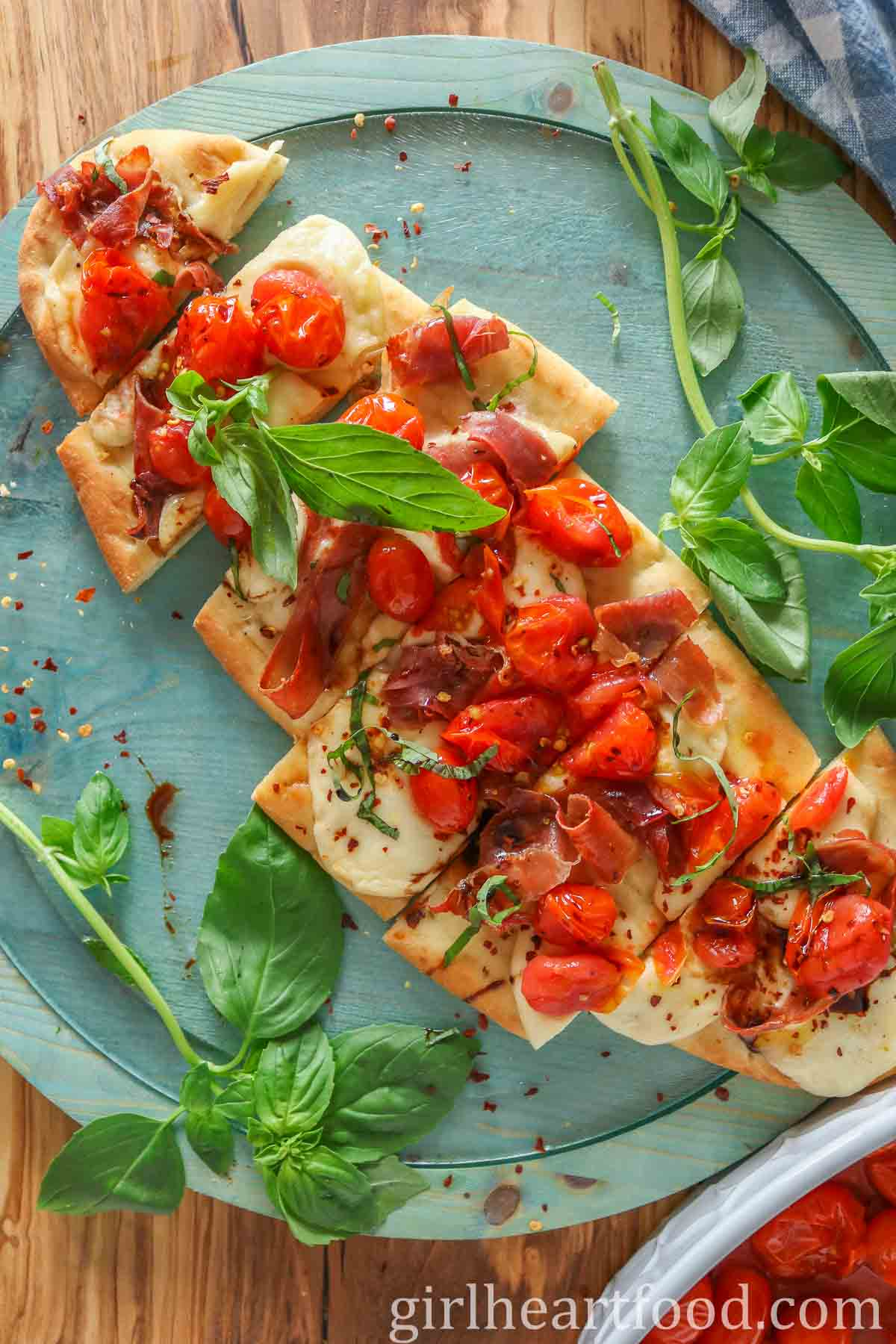 Tomato and prosciutto flatbread pizza, cut into pieces, with basil on either side of it.