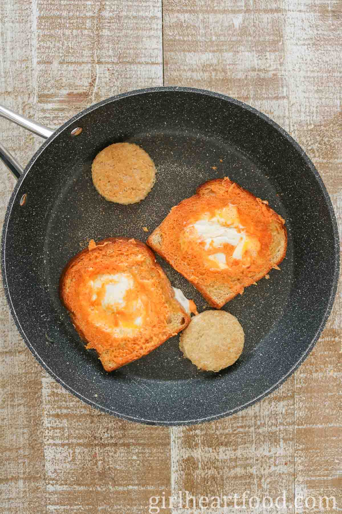 Two cooked portions of egg-in-the-hole toast in a non-stick pan.