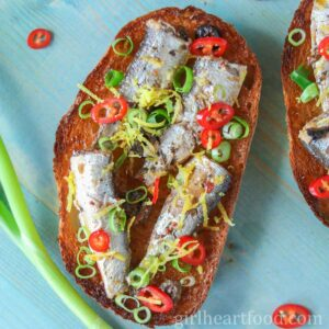 Sardines on toast with chili pepper, lemon zest and green onion next to a stalk of green onion.