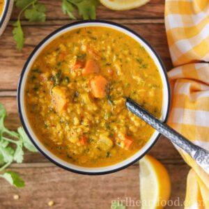 Bowl of split mung bean soup alongside cilantro, lemon and a tea towel.