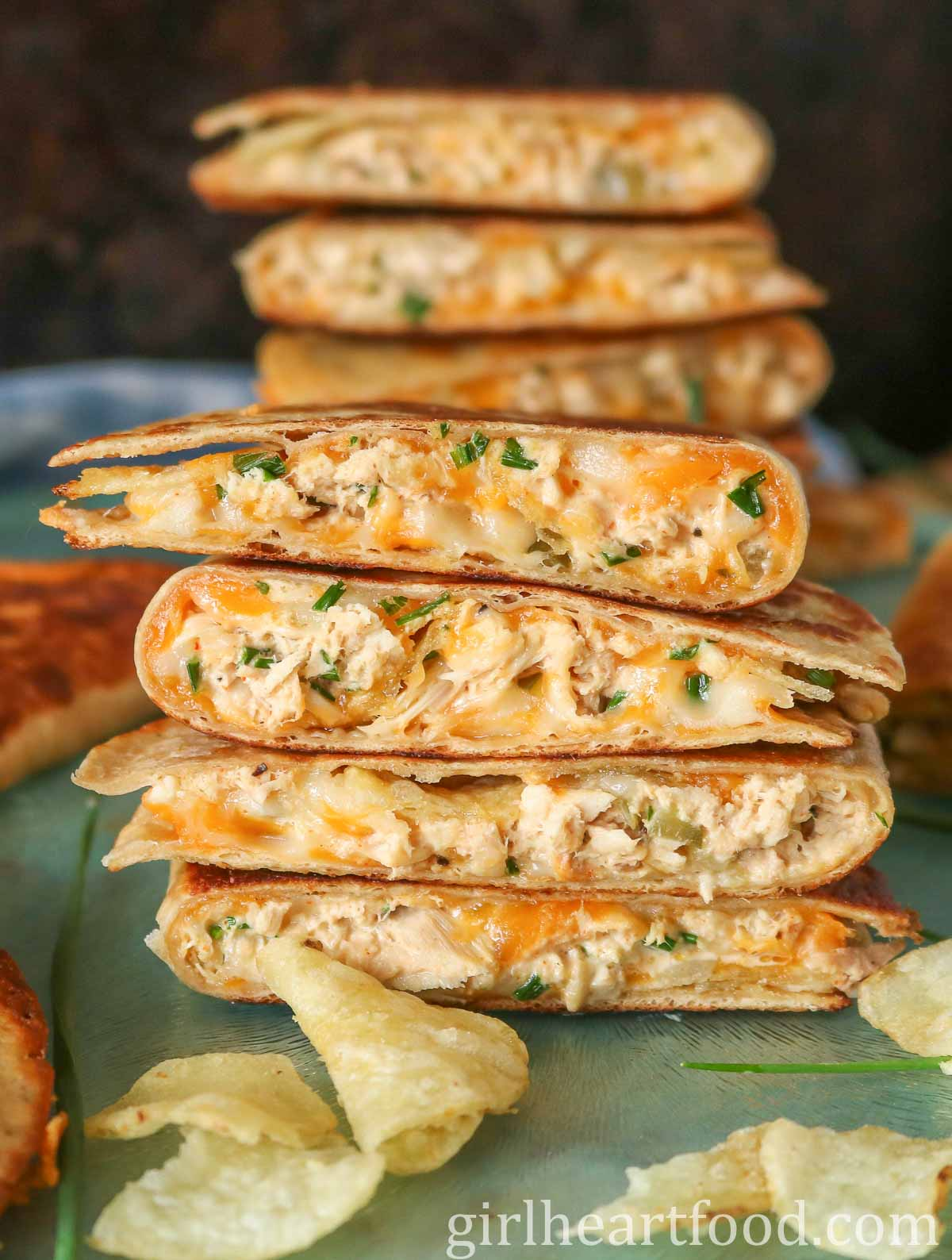 Stack of four cheesy tuna quesadillas with a taller stack of quesadillas behind it.