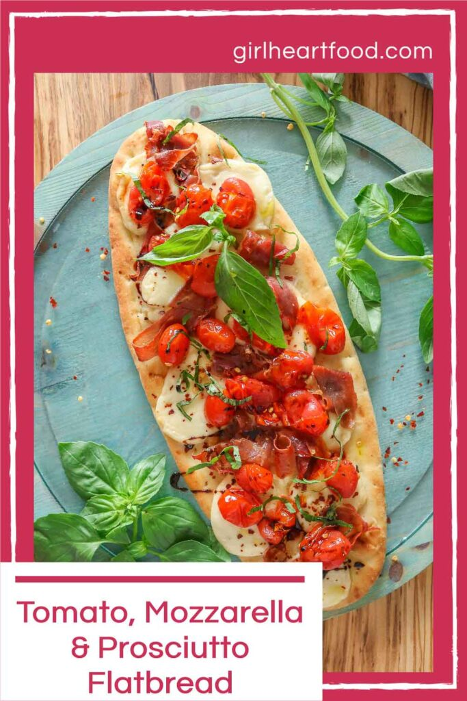 Tomato and prosciutto flatbread pizza with fresh basil on either side of it.