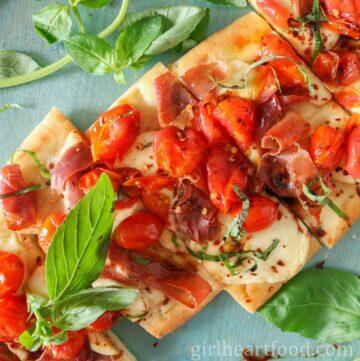 Close-up of a tomato and prosciutto flatbread cut into pieces.