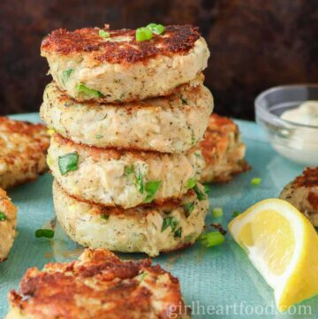 Stack of four tuna fish cakes surrounded by more tuna cakes and a lemon wedge.