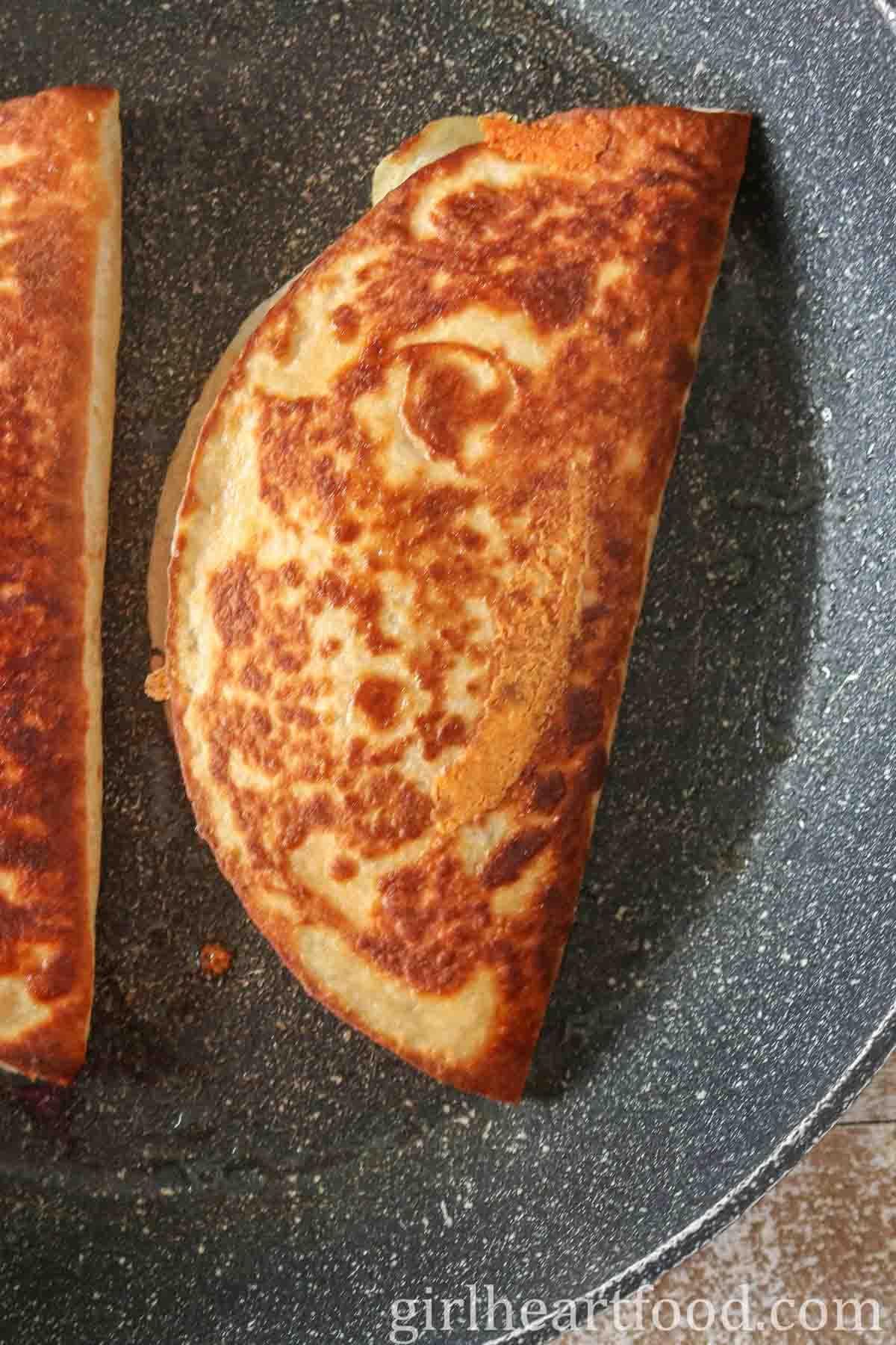 Crispy tuna quesadillas in a non-stick pan.