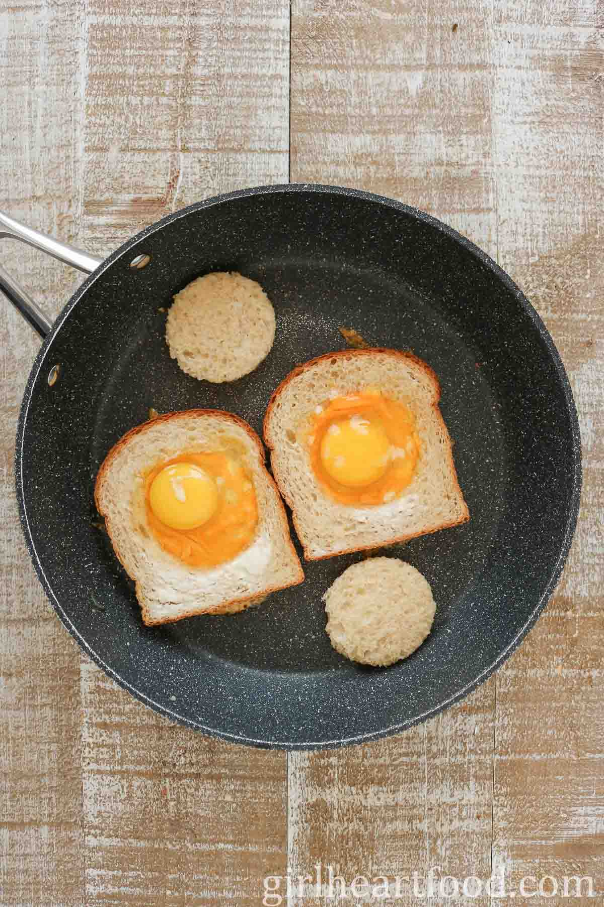 Two portions of egg-in-a-hole in a non-stick pan, not yet cooked.