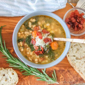 Bowl of veggie, bean and bacon soup next to bread, rosemary and dish of bacon.