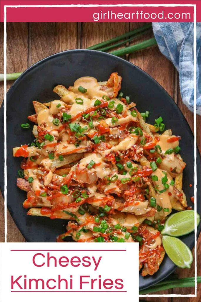 Cheesy kimchi fries and two lime wedges on a black platter alongside green onion.