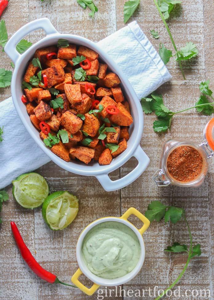 Dish of roasted sweet potato chunks alongside sauce, seasoning, lime, chili pepper & cilantro.