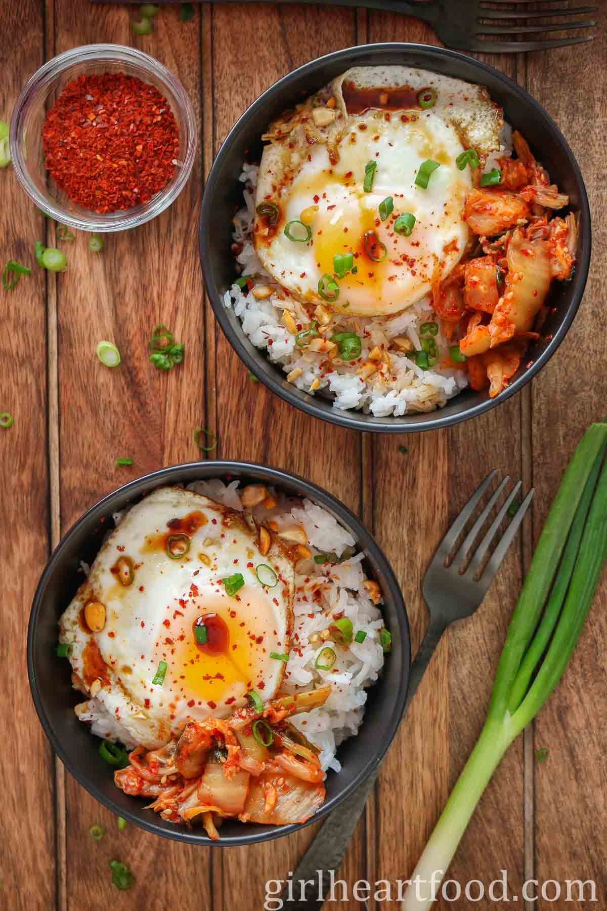 Two fried egg and rice bowls alongside green onion and a small dish of red chili pepper flakes.
