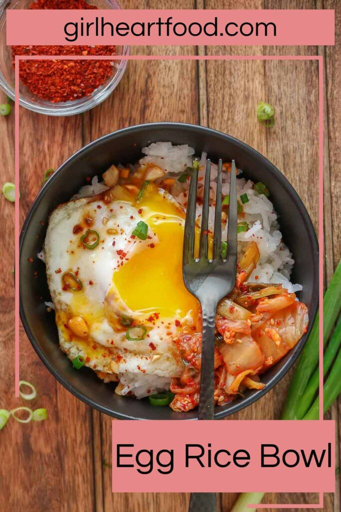Fried egg (with the yolk broke) and rice bowl and a black fork resting on top.