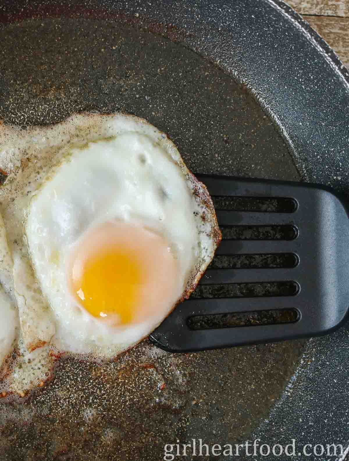 Fried egg in a non-stick pan with a spatula underneath the egg.