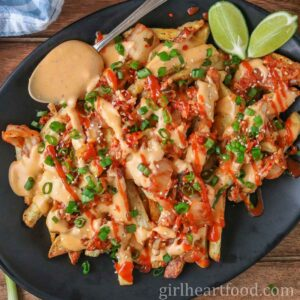 Cheesy kimchi fries, two lime wedges and a spoon with cheese sauce on a black platter.
