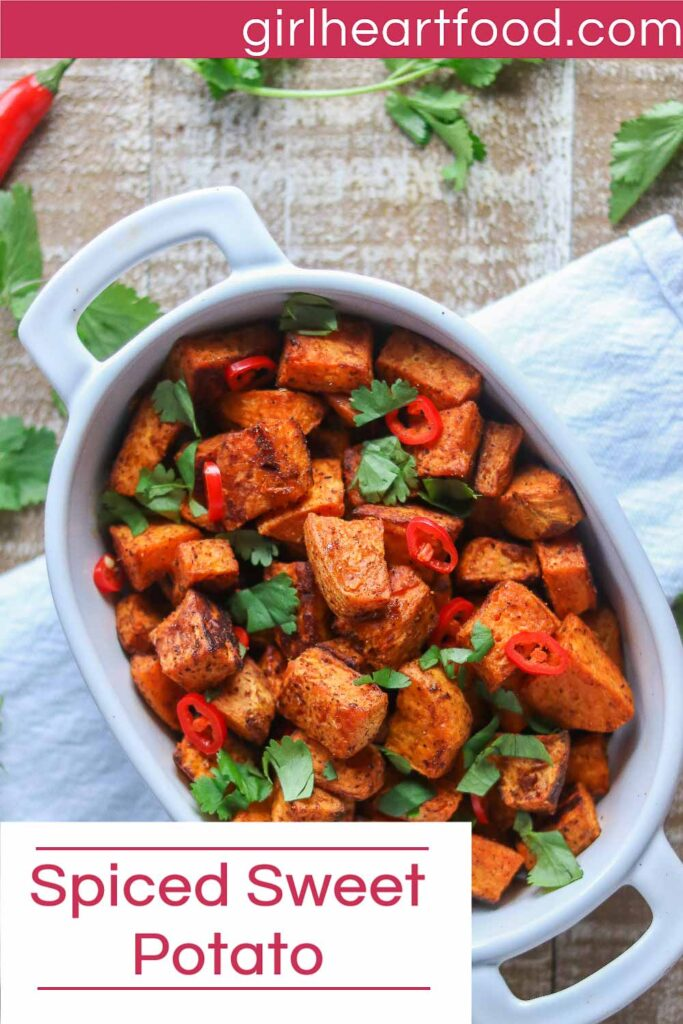 Dish of spiced sweet potato chunks garnished with fresh cilantro and chili pepper.
