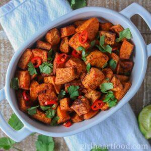 Dish of roasted sweet potato chunks garnished with fresh cilantro and chili pepper.