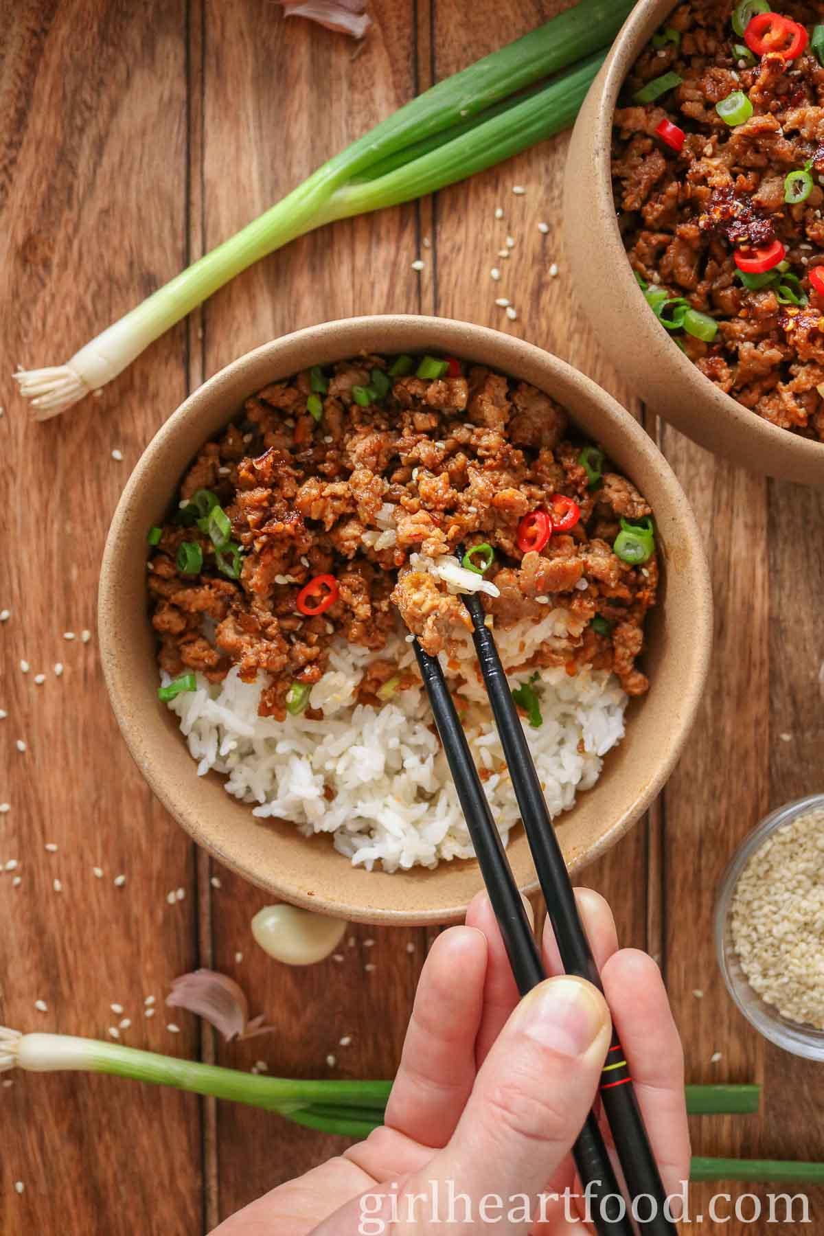 Hand holding chopsticks, eating a turkey rice bowl.