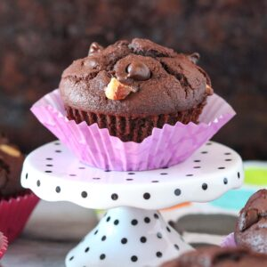 Triple chocolate muffin in a purple liner sitting on a polka dot stand.