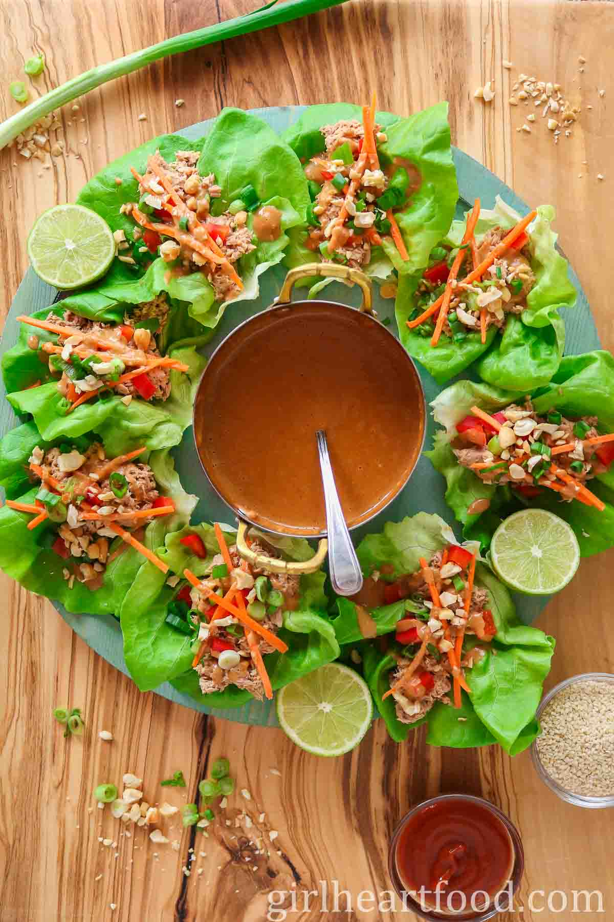 Platter of tuna lettuce wraps with a small pot of peanut sauce in the centre.