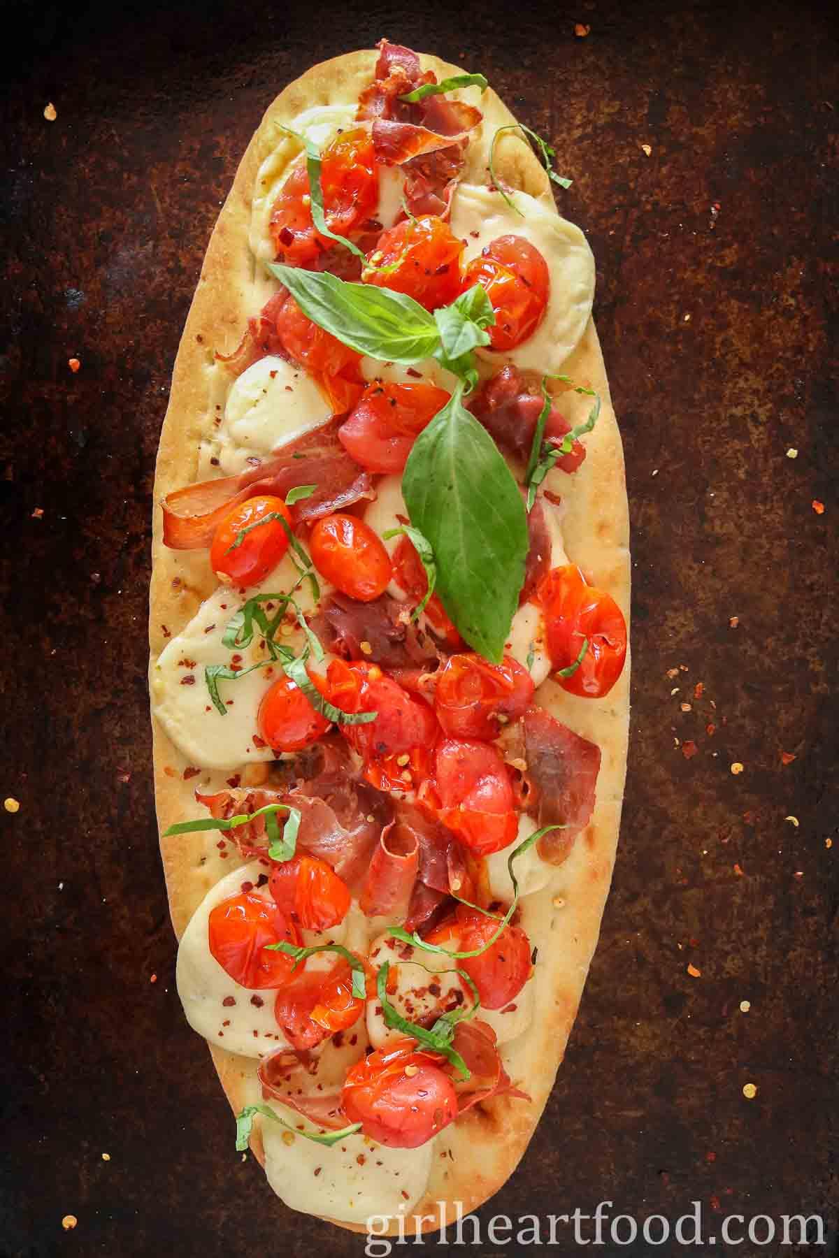 Tomato and prosciutto flatbread pizza on a sheet pan.