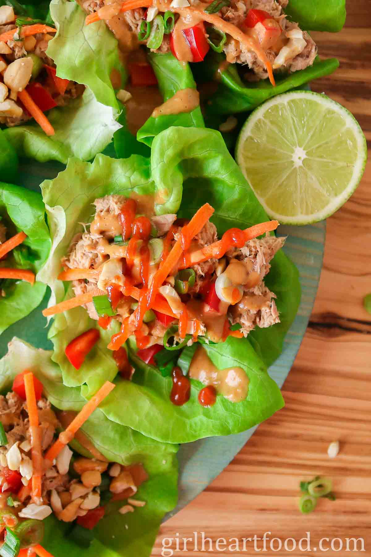 Tuna lettuce wraps with peanut sauce and hot sauce next to half a lime.