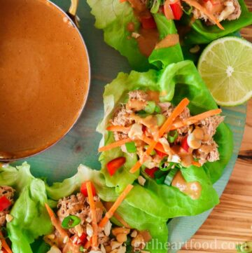 Tuna lettuce wraps with peanut sauce next to a pot of sauce and half a lime.