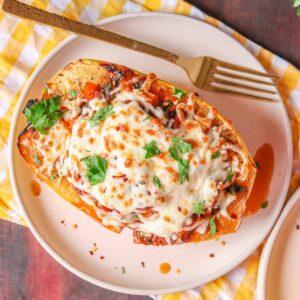 Stuffed spaghetti squash boat on a plate.