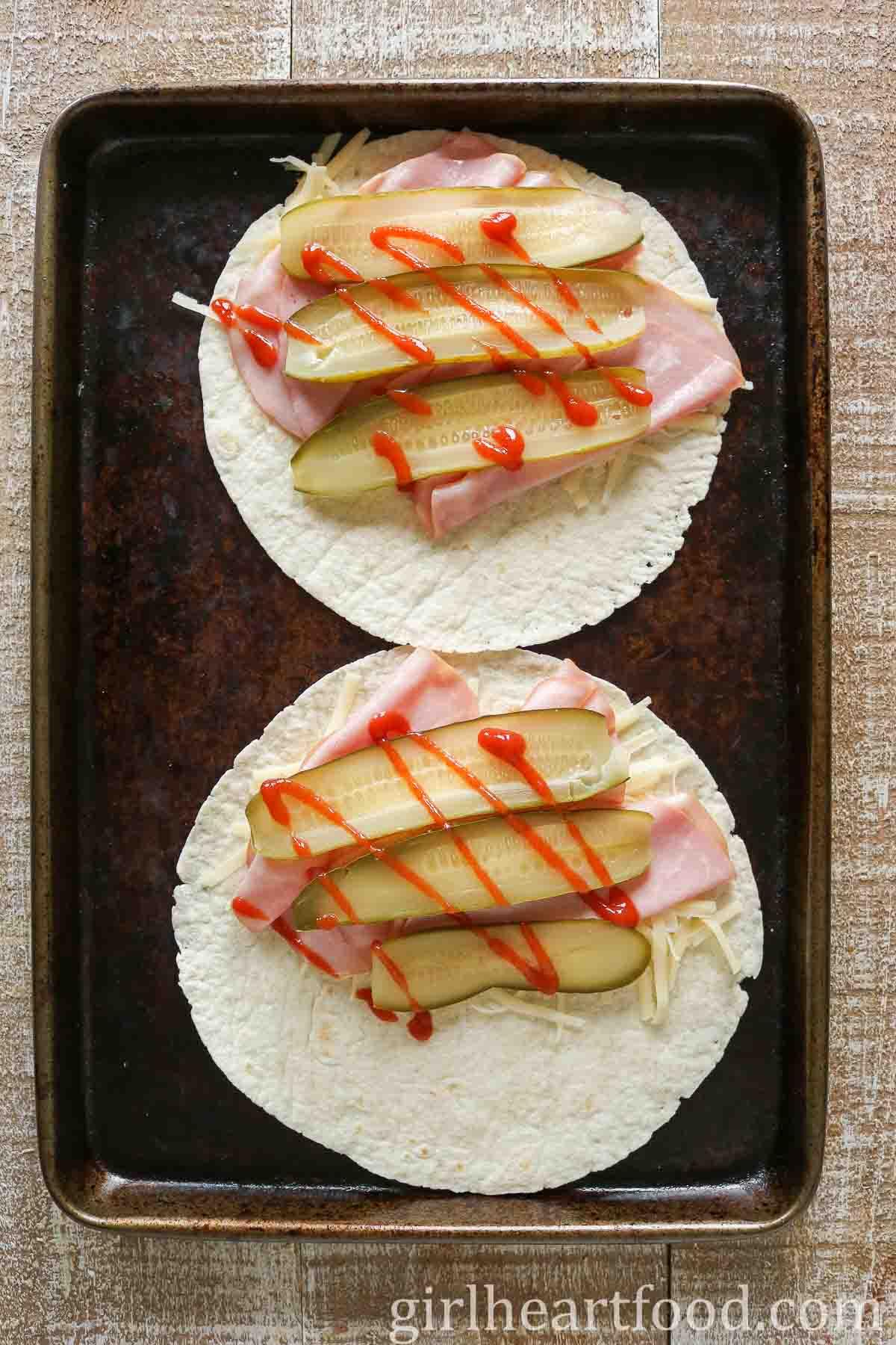 Two tortillas with ham, pickle, cheese and hot sauce on a sheet pan.