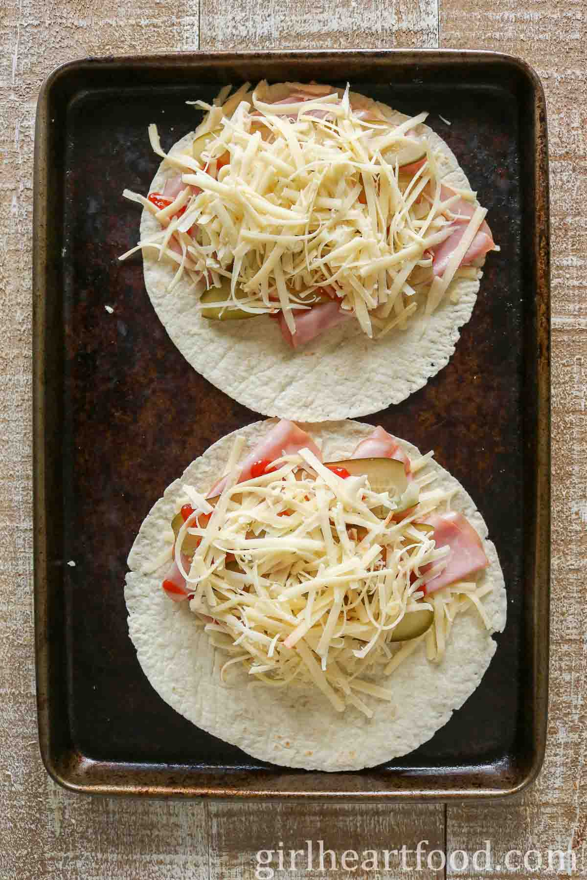 Two ham, pickle and cheese quesadillas on a sheet pan before being folded over and pan fried.