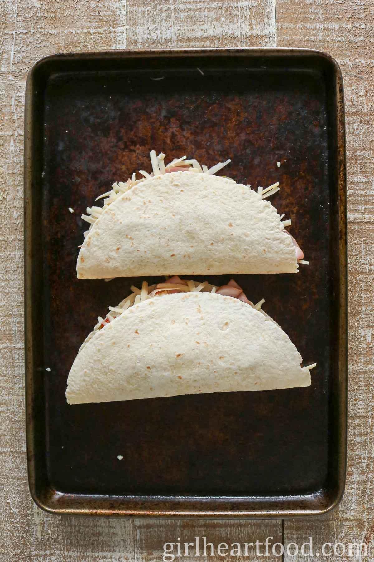 Two quesadillas on a sheet pan before pan frying.