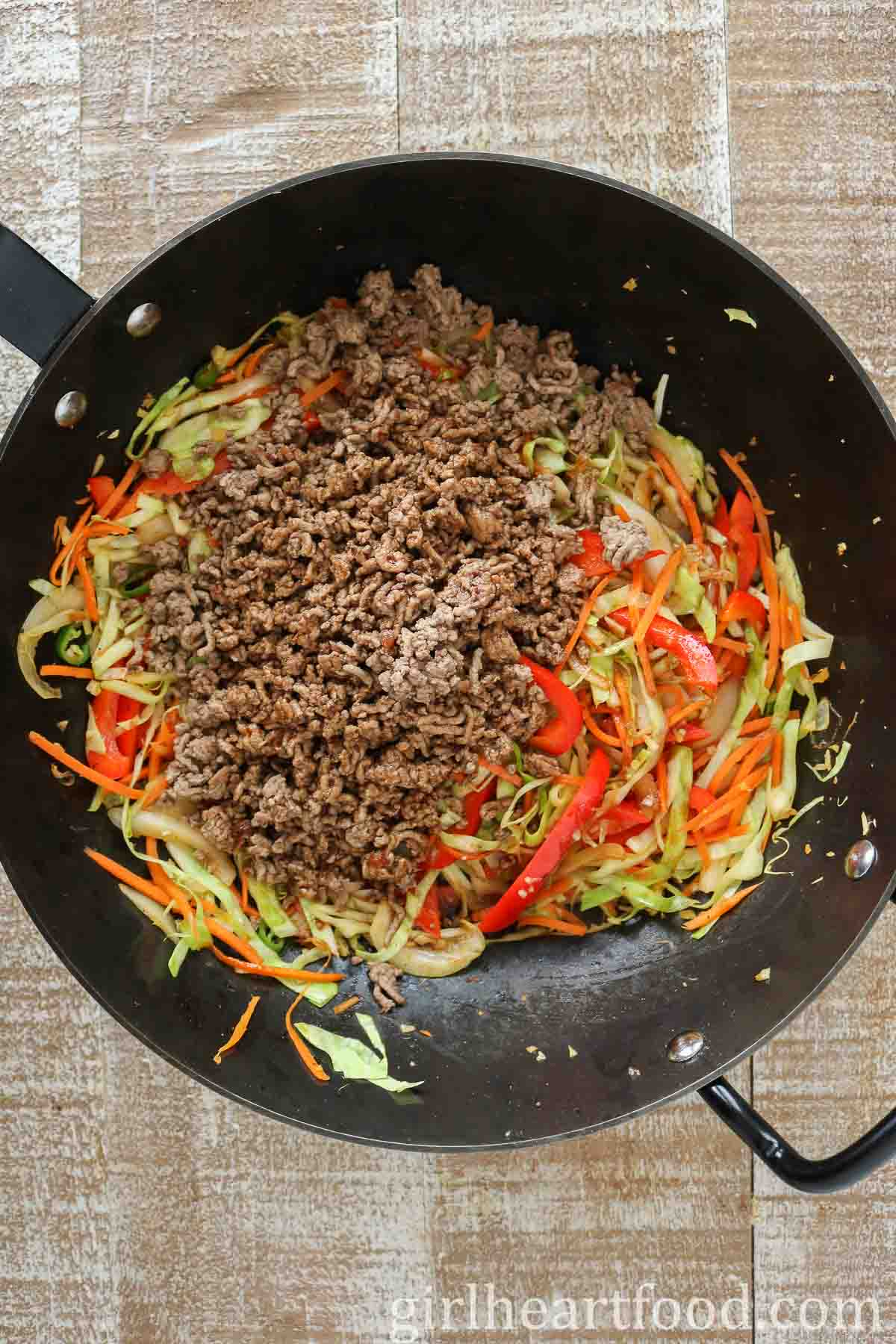 Cooked ground beef and vegetables in a wok before being mixed together.